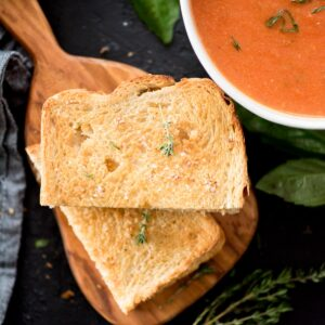 air fried grilled cheese sandwich sliced in half on a cutting board next to a bowl of soup and topped with a sprig of fresh thyme
