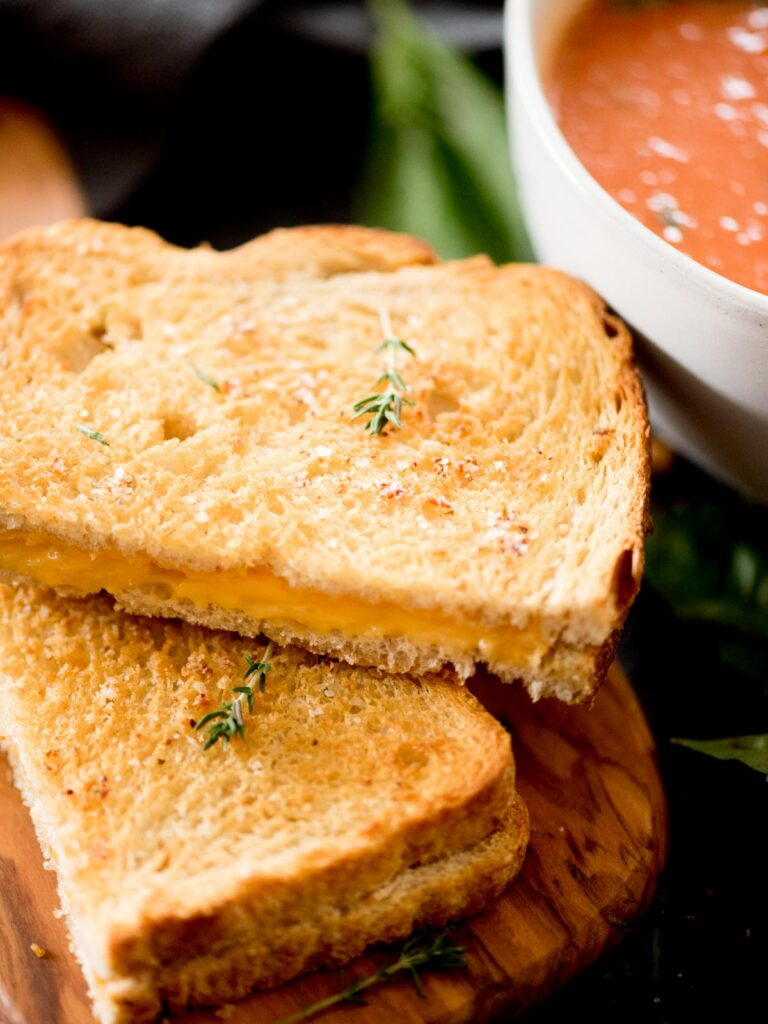 air fried grilled cheese sandwich cut in half next to a bowl of tomato basil soup and topped with a small sprig of thyme