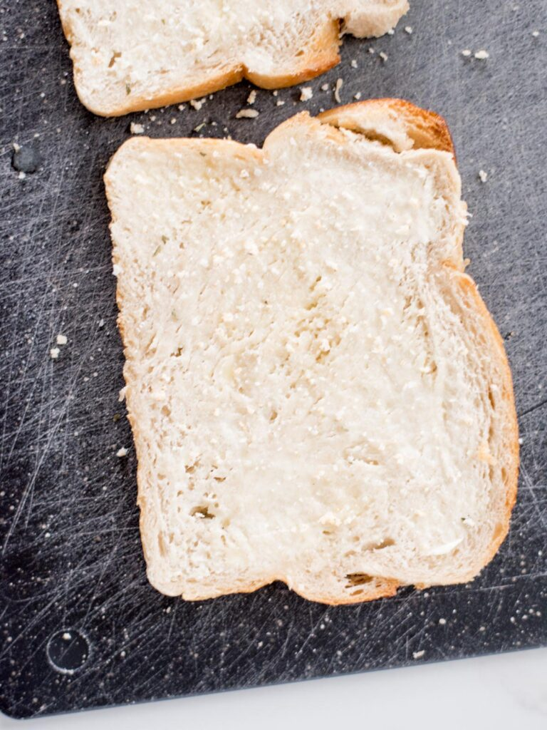 slice of buttered bread on a cutting board sprinkled with garlic salt