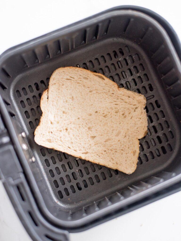 slice of buttered bread, butter side down in an air fryer basket