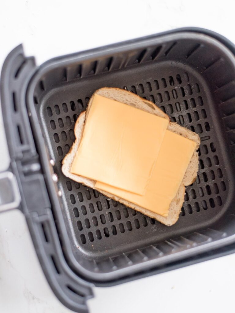 two slices of cheese on a piece of bread inside the air fryer basket