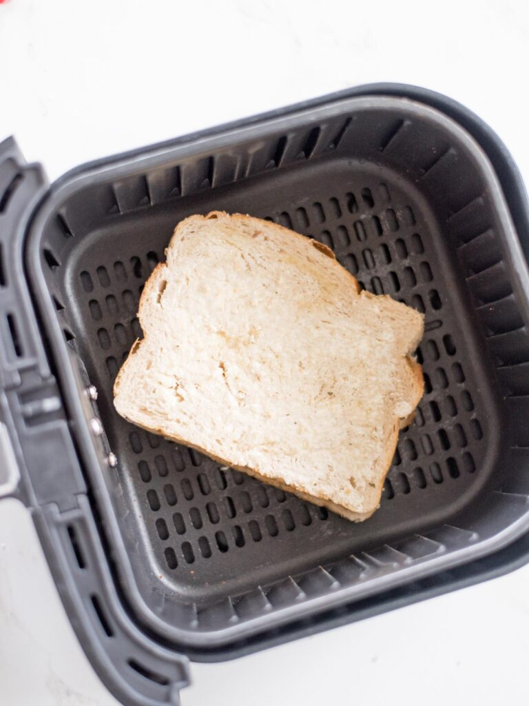 uncooked cheese sandwich with buttered bread sitting inside an air fryer basket