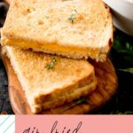 """pinterest graphic with text stating """"air fried grilled cheese sandwich"""" with a picture of a sliced grilled cheese sandwich next to a bowl of tomato basil soup"""