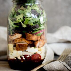 cobb style mason jar salad with lid on and a fork sitting next to it