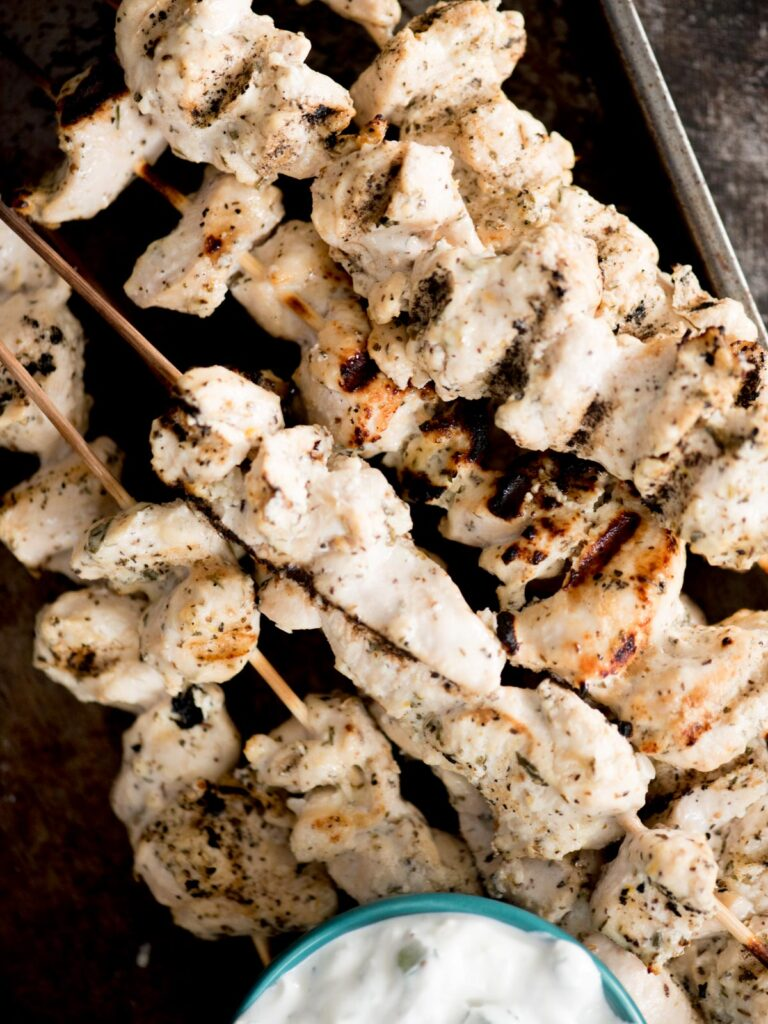greek grilled chicken skewers stacked together with tzatziki sauce