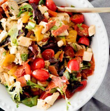 pesto chicken mason jar salad in a bowl with a fork
