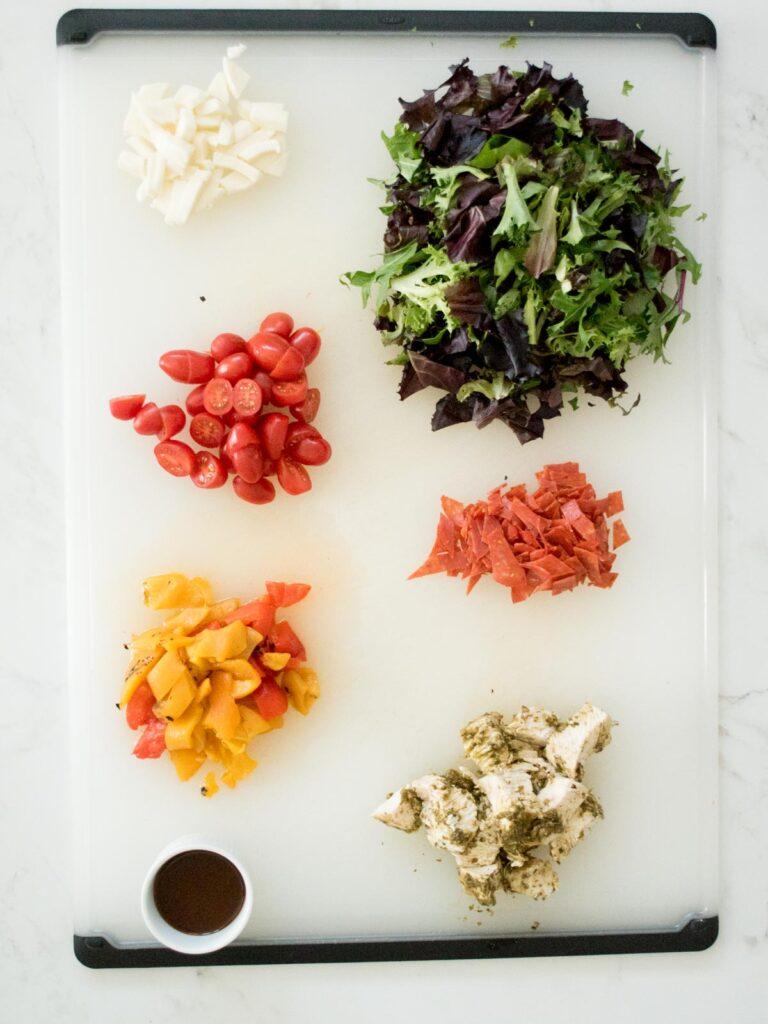ingredients on a cutting board for pesto chicken mason jar salad