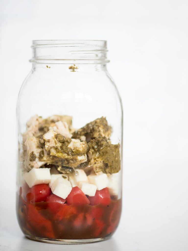 balsamic vinaigrette, roasted peppers, grape tomatoes, basil pesto chicken, and mozzarella in a jar