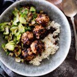 sticky sweet chicken meatballs in a bowl with rice and brussels sprouts