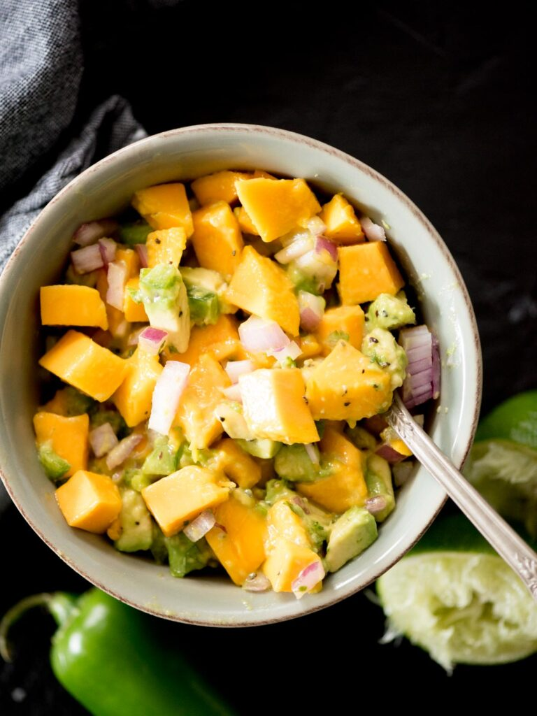 avocado mango salsa in a bowl being spooned out
