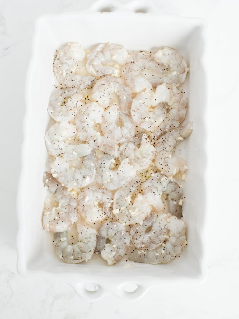 shrimp, garlic, and wine mix in a baking dish topped with salt and pepper