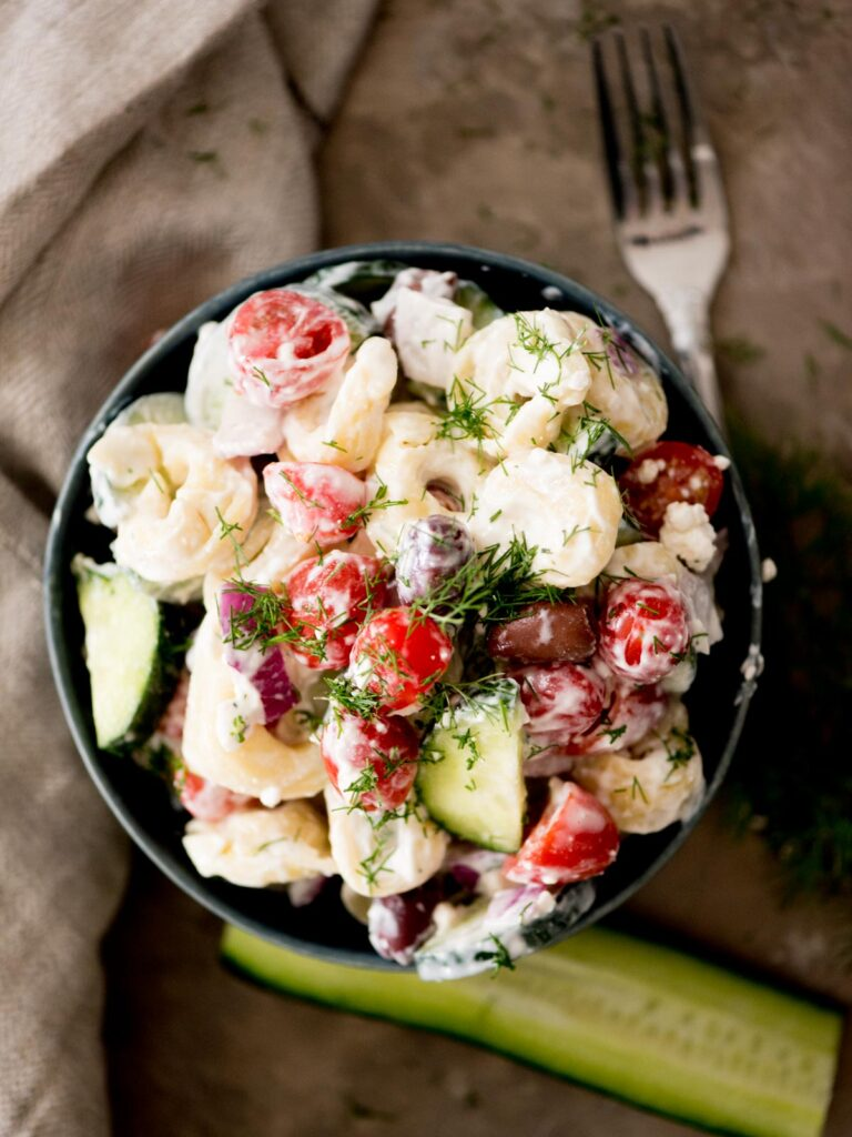 greek pasta salad in a bowl topped with fresh dill