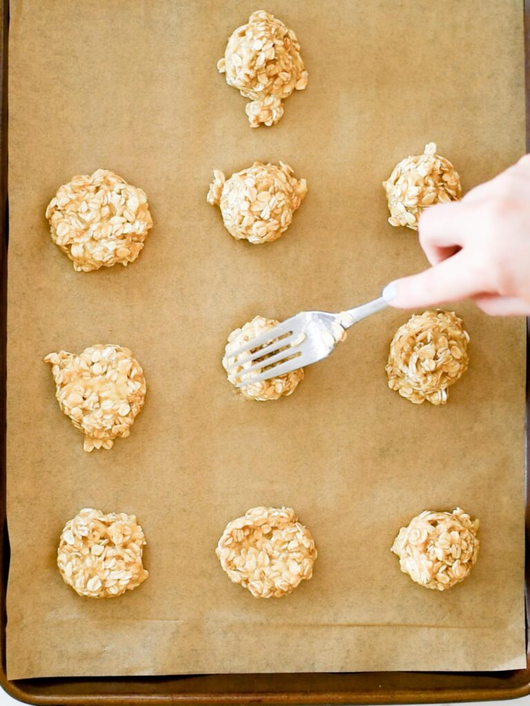 cookie dough being gently pushed down with a fork on a parchment lined baking sheet