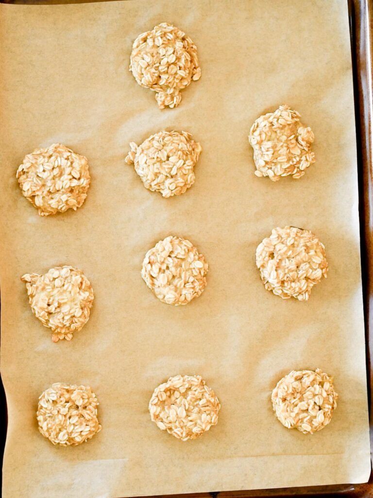 healthy banana oatmeal cookies on a parchment lined baking sheet