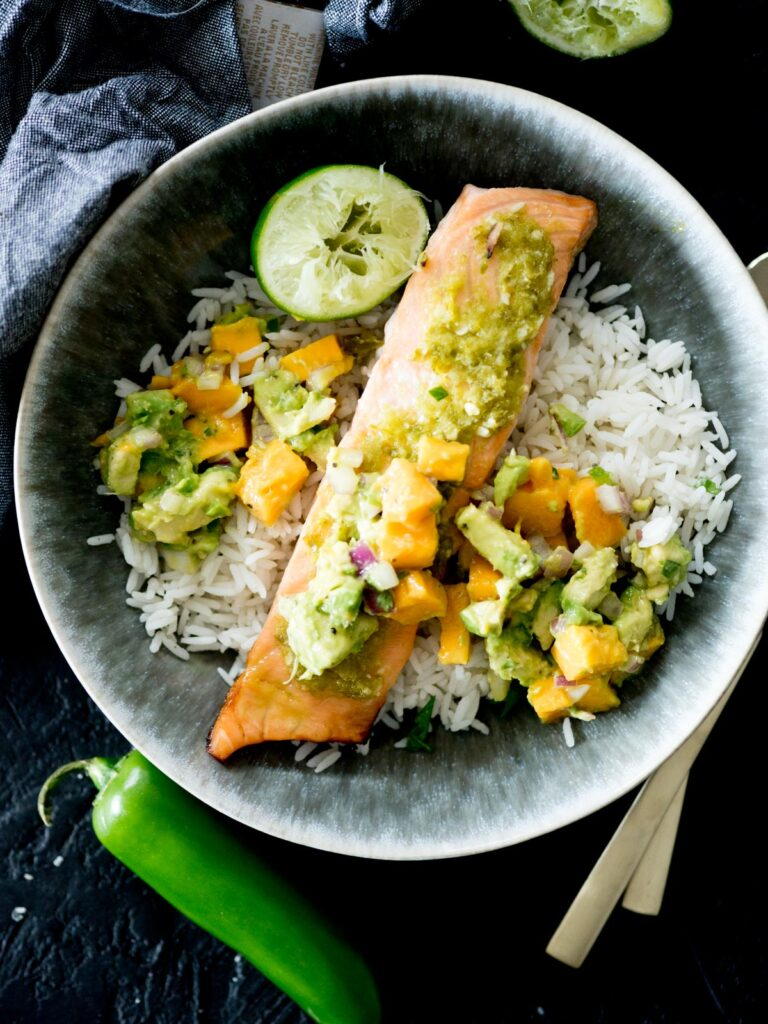 honey jalapeno lime salmon in a bowl with jasmine rice, mango avocado salsa, and a squeezed lime