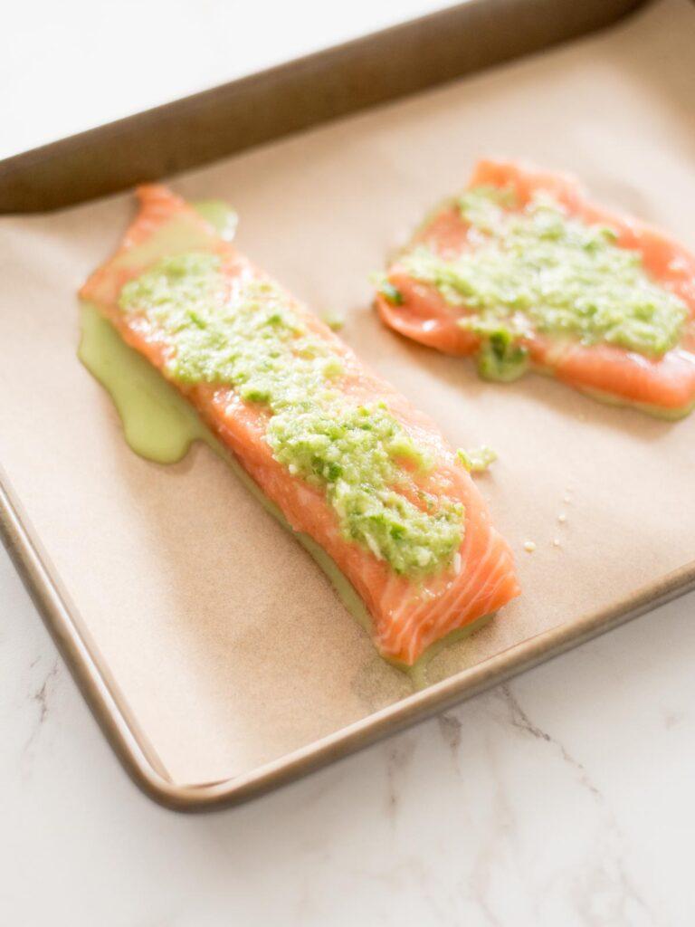 honey jalapeno lime mix on salmon filets on a parchment lined baking sheet