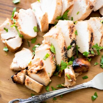 sliced marinated grilled chicken on a cutting board