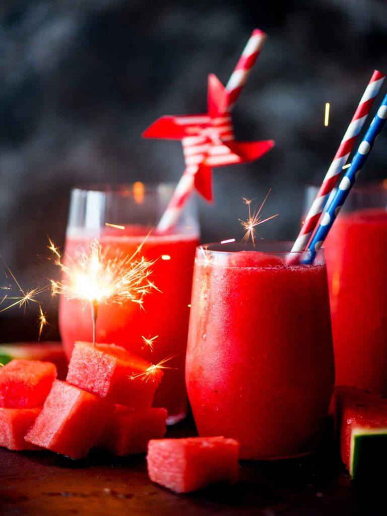 watermelon slush in glasses with paper straws and frozen watermelon chunks. Sparkler in watermelon
