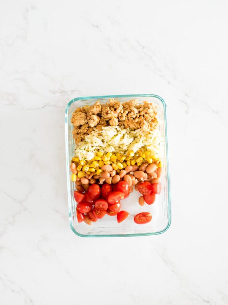 turkey, rice, corn, beans, and tomatoes added to a glass container