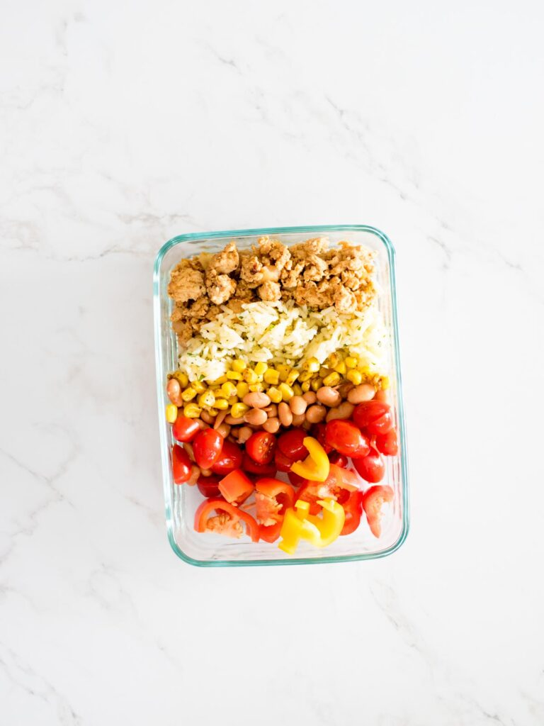 turkey, rice, corn, beans, tomatoes, and peppers added to a glass container