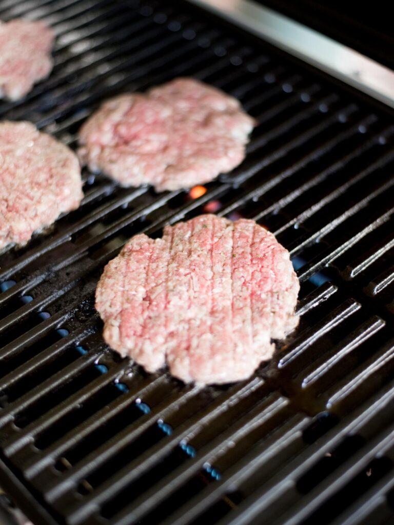 raw hamburger patties on the grill