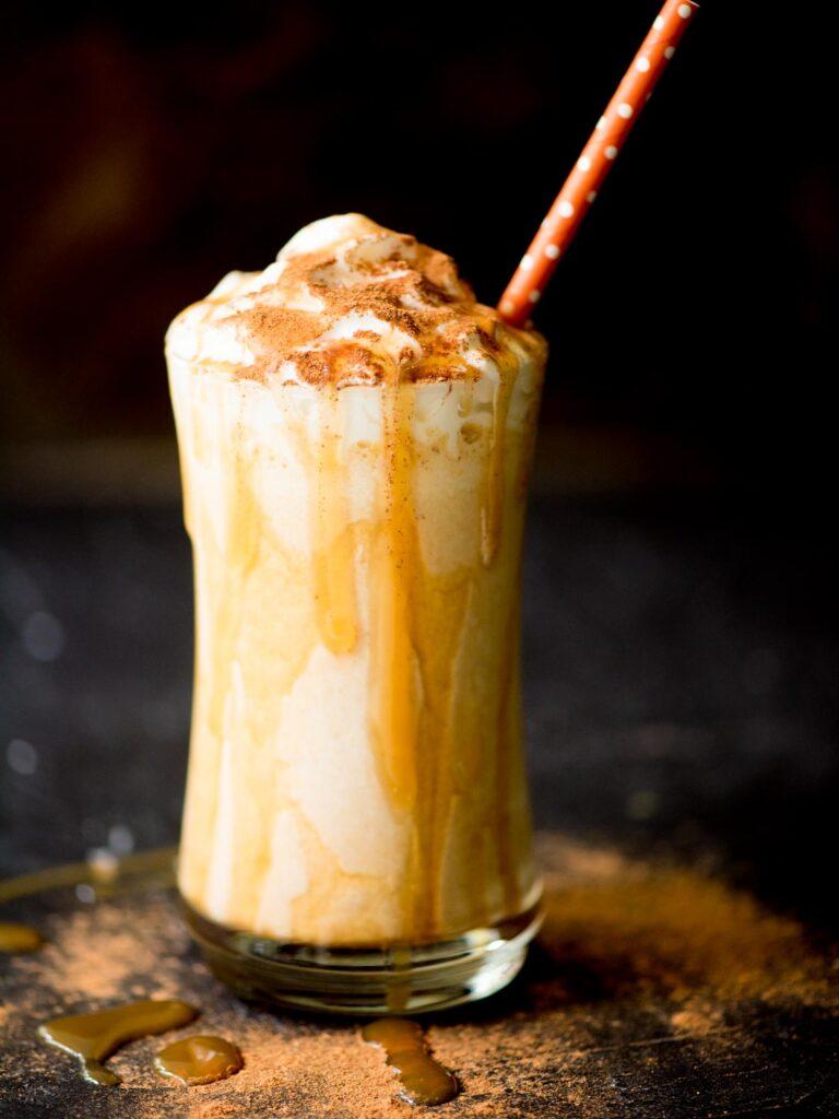 pumpkin milkshake in a glass with a caramel drizzle