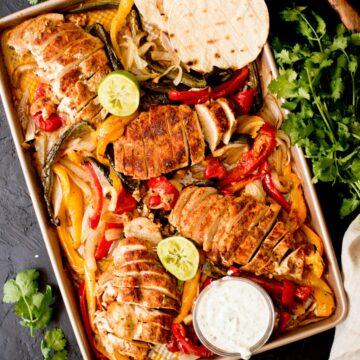 sheet pan chicken fajitas with creamy cilantro lime sauce, tortillas, and limes