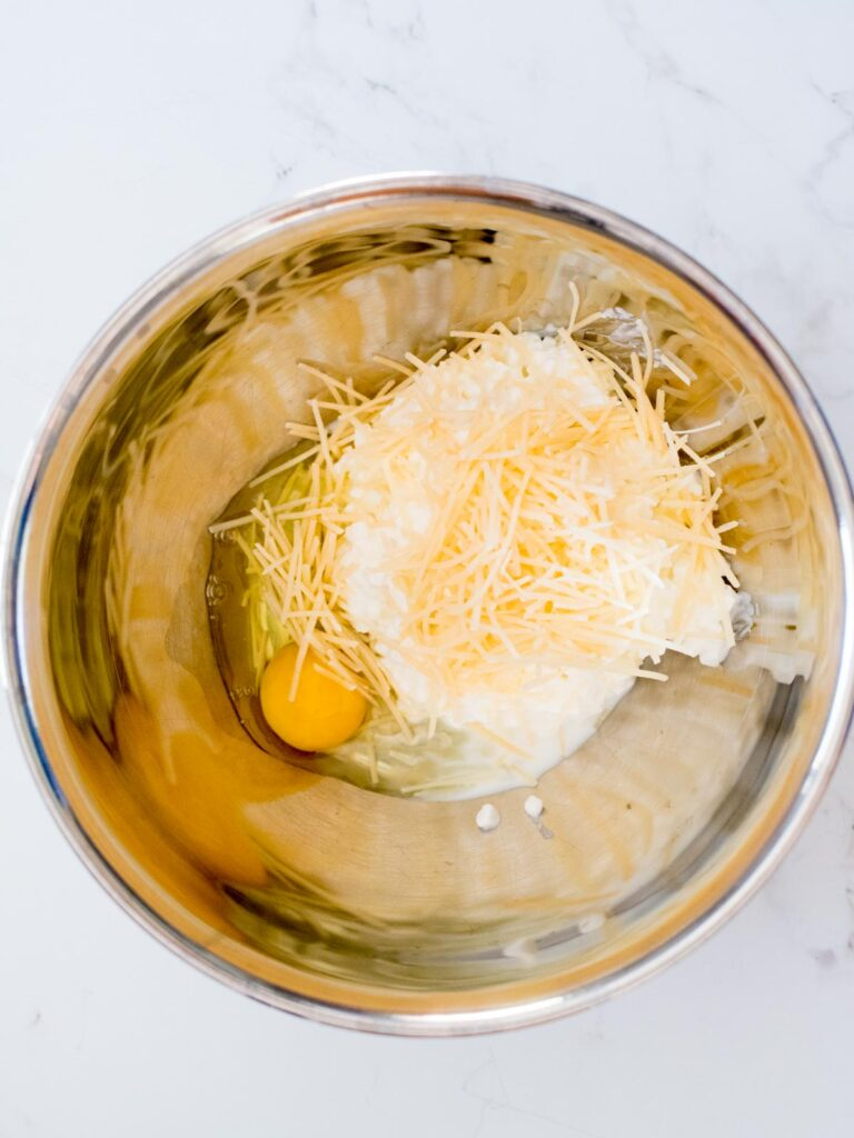 egg added to cottage cheese and parmesan in a mixing bowl