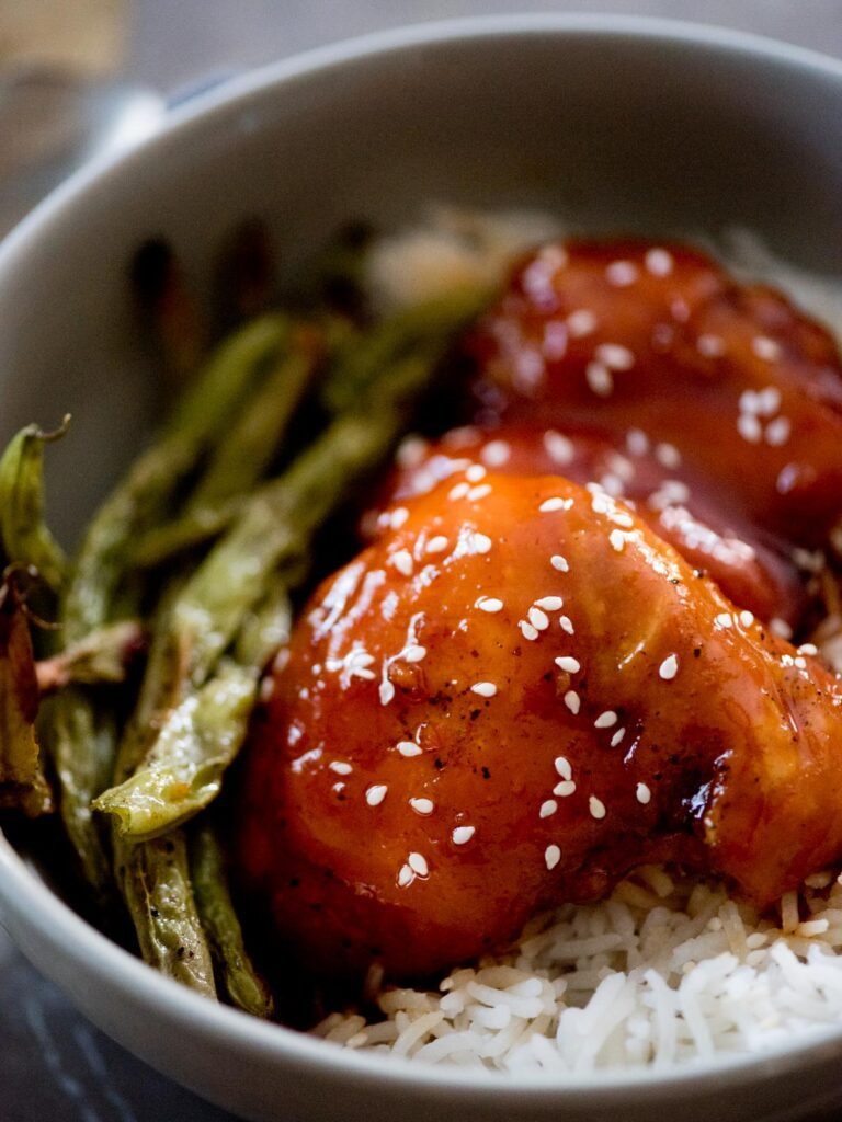 honey garlic chicken topped with sesame seeds over rice and green beans