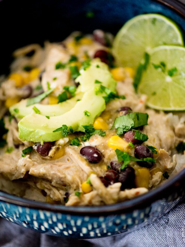 salsa verde chicken in a bowl over rice topped with avocado and lime