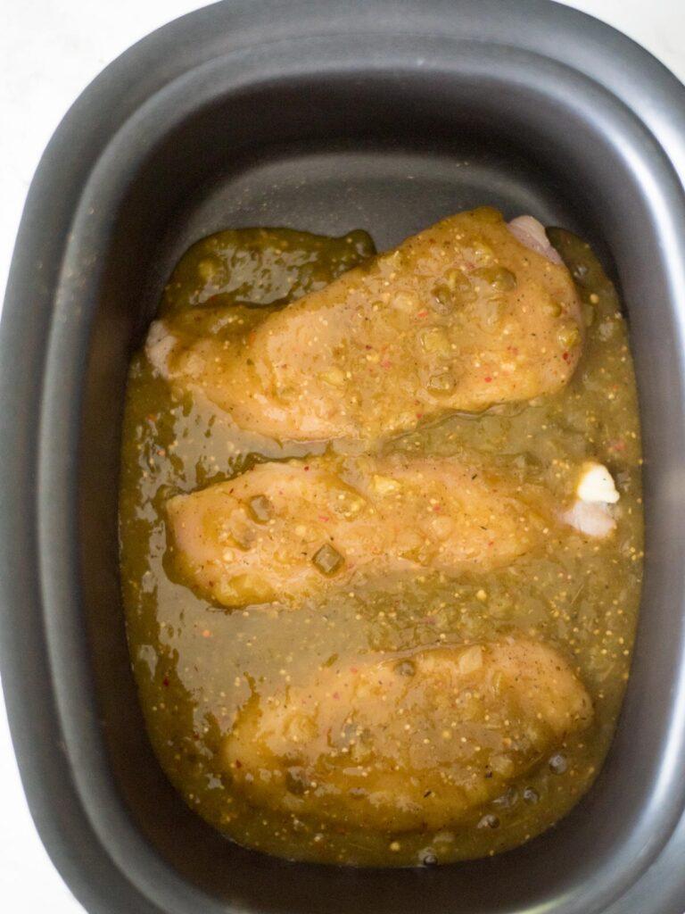 seasoned chicken in the crockpot covered in salsa verde