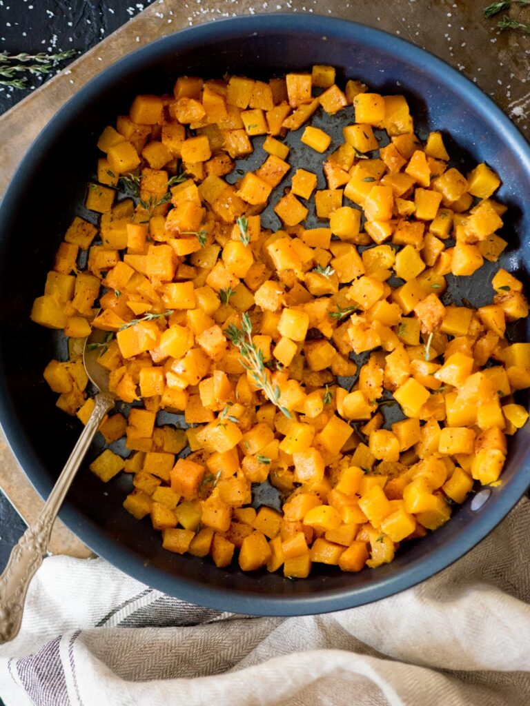 sauteed butternut squash in a skillet topped with fresh thyme